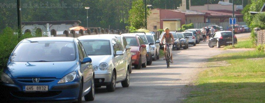 řada aut zaparkovaných kolem celé plovárny